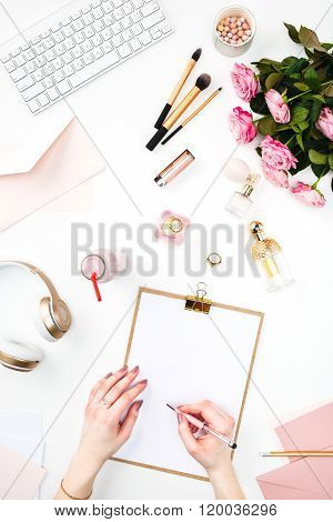 The female hands writing against fashion woman objects