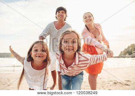 Family walking on the evening beach during sunset, travel photo series