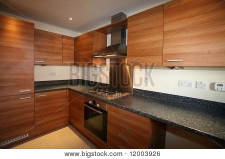 Interior of galley-style kitchen with integrated appliances __ selective focus on center