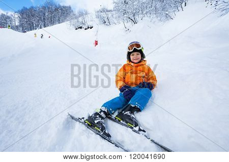 Little boy rest after ski lesson sitting in snow