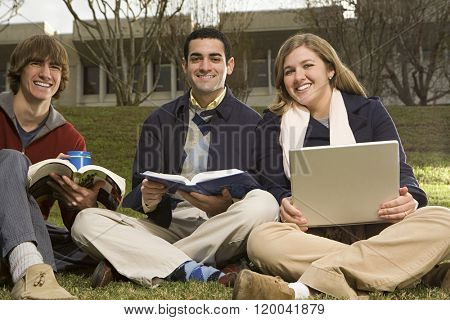 Three students sat outdoors