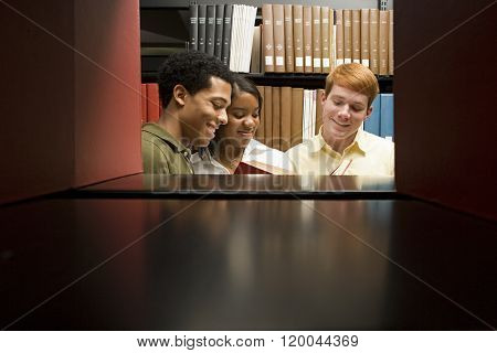 Three students reading in the library