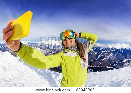 Woman take selfie over mountain and ski tracks