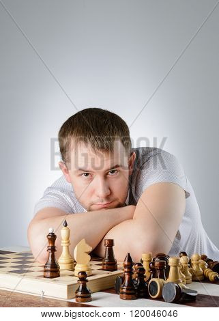 Man Lying On The Folded Hands Of Chess Board
