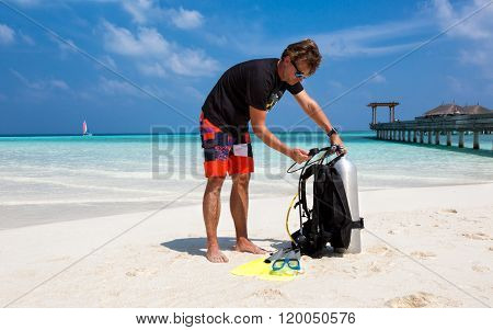 Male scuba diver checking his oxygen tank