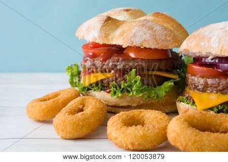 Homemade burgers and onion rings. Blue background