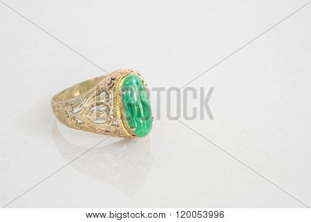Closeup old green jade ring on blurred marble stone floor texture background