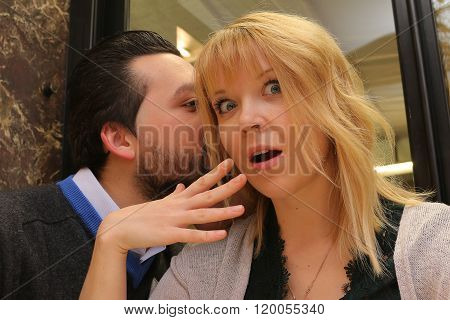 woman surprised while man whispers in her ear