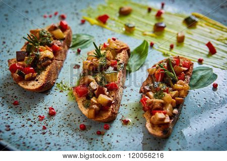 Vegan food: bruschetta with bell pepper, tomatoes, arugula, thyme and basil