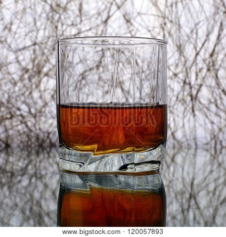 Tumbler of whiskey or brandy on original background with reflection