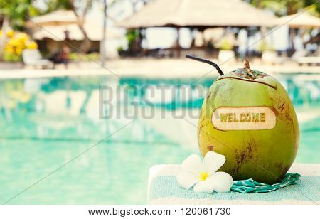 Green coconut with carving welcome on a swimming pool summer background Copy space