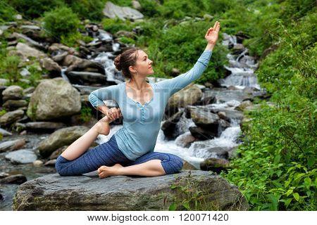 Young sporty fit woman doing yoga asana Eka pada rajakapotasana - one-legged king pigeon pose at tropical waterfall. Himachal Pradesh, India