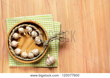 Braid of garlic on wooden table.