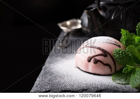Individual mousse cake in the form of hemisphere covered with pink glaze with mint leaves on dark background. Holiday food concept with copy space for text. ** Note: Shallow depth of field