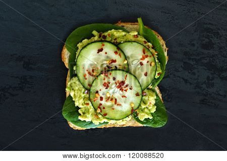 Avocado sandwich with cucumber and spinach on dark slate