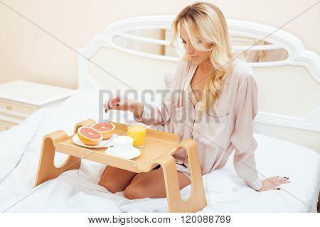 young beauty blond woman having breakfast in bed early sunny morning, princess house interior room