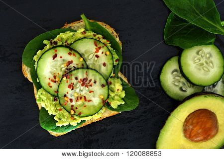 Avocado sandwich with cucumber and spinach on dark slate background