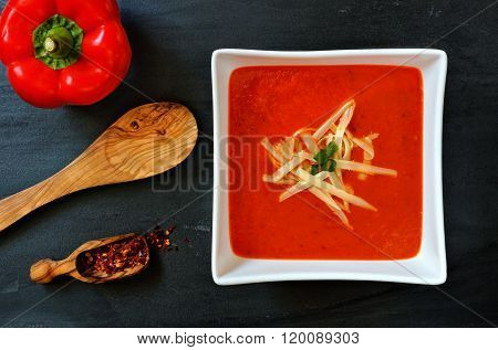 Red pepper soup overhead scene on slate background