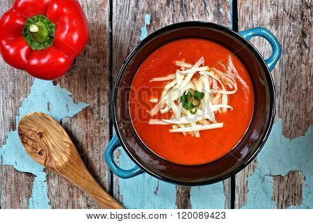 Red pepper soup overhead scene on rustic blue wood background