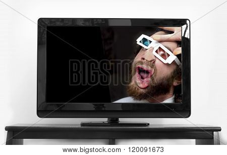 Silly bearded man wearing 3D glasses stuck inside TV screen