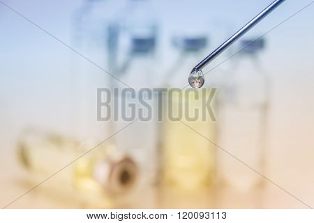 Needle Of Syringe With Ampules On Bicolor Blurred Background