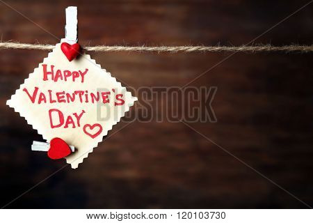Valentine's Day card with hearts and words of love on wooden background