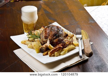 pork shank with roasted potatoes and glass of beer