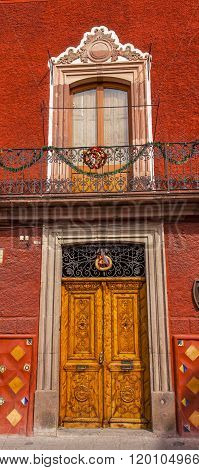 SAN MIGUEL DE ALLENDE, MEXICO - DECEMBER 27, 2014 Golden Brown Wooden Door Christmas Wreath Window Red Wall Jardin San Miguel de Allende Mexico