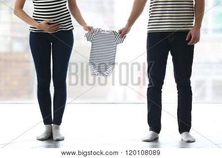 Pregnant woman with husband holding child's clothes in front of the window