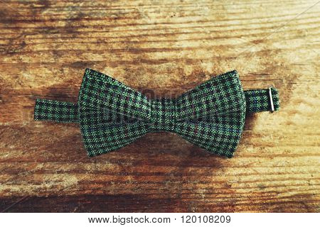 Green bow tie on wooden background