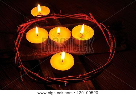 closeup of a recreation of the crown of thorns of Jesus Christ and some lit candles on a wooden cross