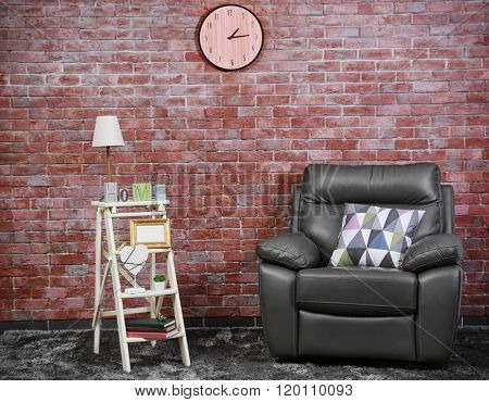 Brown leather armchair and white bookshelf against brick wall background