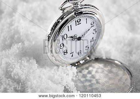 Pocket watch over white snow background