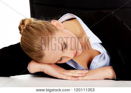 Overworked business woman sleeping at the desk in office