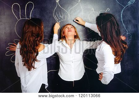 Teachers re-drawing chalk his colleague