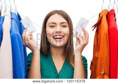 clothing, fashion, sale, shopping and people concept - happy woman showing price tags on clothes at home wardrobe or shop