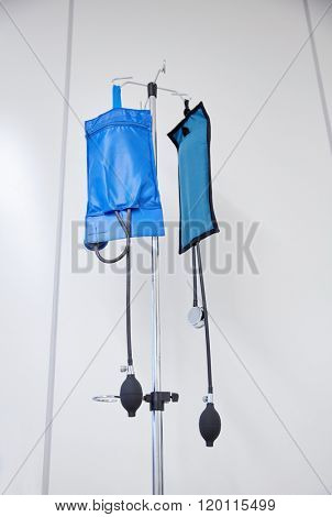 medicine, health care and medical equipment concept - two sphygmomanometers or pressure infusion cuffs hanging on holder at hospital