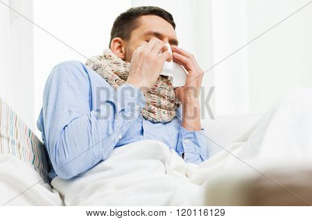 healthcare, flu, people, rhinitis and medicine concept - close up of ill man blowing his nose with paper napkin at home