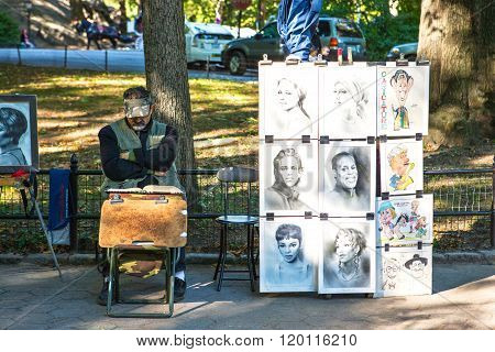 New York, U.S.A. - October 10, 2010: Manhattan, a painter relaxes near his works, in Central Park.