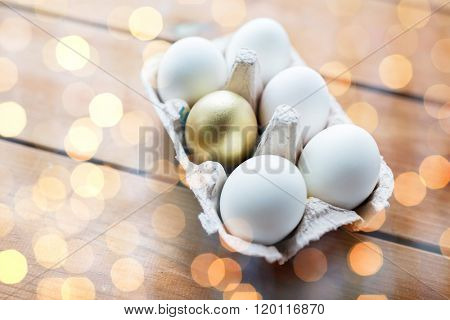 easter, food, cooking and object concept - close up of white and golden eggs in egg box or carton wooden surface over lights