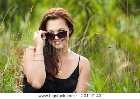 Woman looking over the top of sunglasses