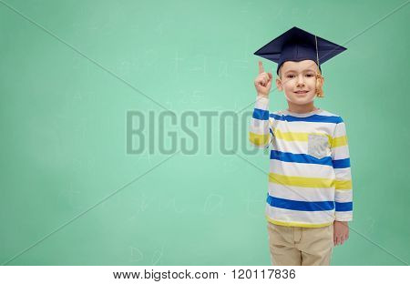 childhood, school, education, learning and people concept - happy boy in bachelor hat or mortarboard pointing finger up over green chalk board background