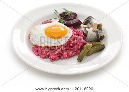 homemade labskaus, Northern Germany cuisine. labskaus with fried egg, pickled gherkin, beetroot and rollmops.