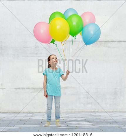 childhood, fashion, imagination and people concept - happy little girl looking up and holding bunch of colorful helium balloons on strand over concrete wall on street background