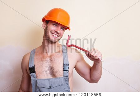 Man In Overalls With A Tool For Dismantling