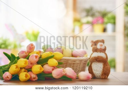 Happy Easter! Easter background with colorful eggs in basket, yellow and pink tulips and rabbit. Easter decoration with rabbit and eggs. Easter symbols: Bunny and eggs.