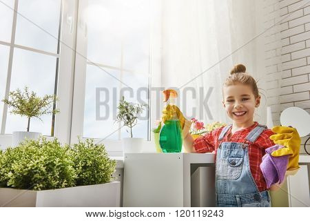 Charming little helper. Cute little child girl makes cleaning the house. Girl rubs dust.