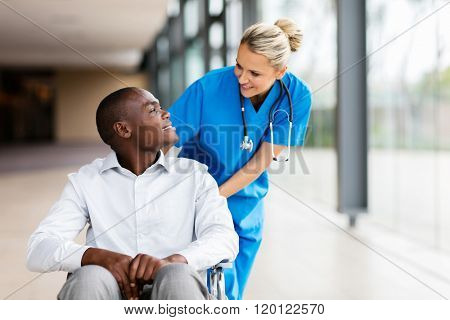 caring female nurse talking to disabled patient in hospital