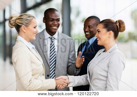 cheerful business team welcoming businesswoman