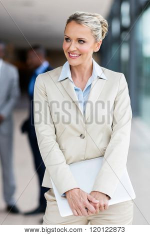 gorgeous mid age corporate worker holding laptop in office